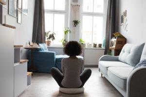 femme assis en tailleur de dos dans une salon blanc